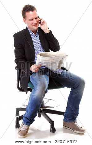 Full length businessman reads newspaper phoning talking on mobile phone commenting economy news isolated on white background