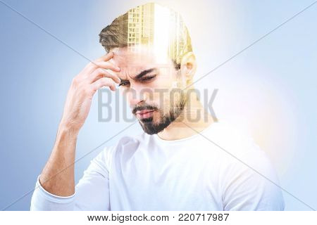 Thoughtful look. Nice thoughtful young man holding his forehead and imagining the city building while thinking about them