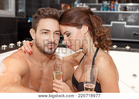 Young couple with champagne in jacuzzi, honeymoon