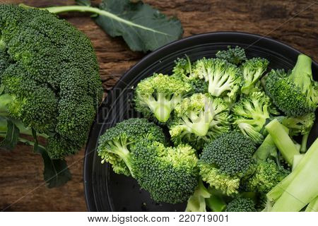 Healthy Green Organic Raw Broccoli Florets Ready for Cooking. Raw fresh broccoli on wooden table.