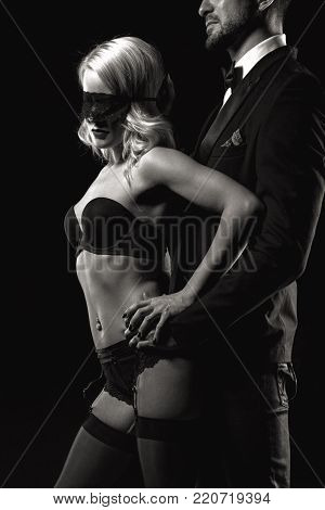 Stylish man touching sexy blonde lover in blindfold closeup black and white, sensuality and foreplay