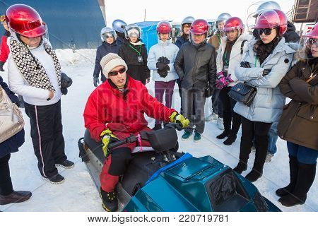 Hokkaido, Japan - 29 December 2017 - Snow mobile renter explains to his customers how to operate the vehicle in Hokkaido, Japan on December 29, 2017
