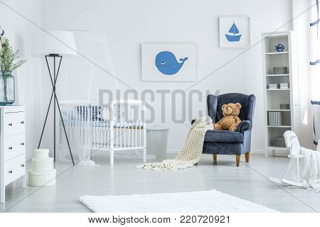 Crib Between Armchair And Lamp