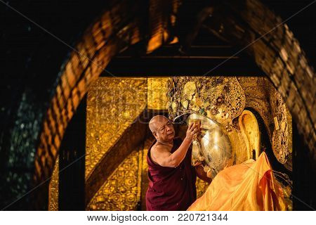 MANDALAY, MYANMAR - DECEMBER 11, 2017 : Senior monk wash the face of Mahamuni Buddha image every morning at Mahamuni temple in Mandalay, Myanmar.