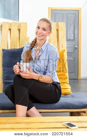 Pretty businesswoman drinking hot morning coffee and dreaming in modern loft. Woman in businness. Freelancer in coworking center is resting and enjoying the drink. Freelance work concept