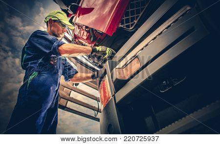 Semi Truck Maintenance. Caucasian Truck Service Worker in His 30s Performing Scheduled Recall Maintenance.