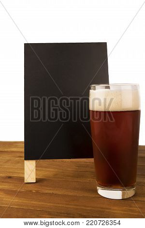 Glass of beer and blackboard disposed on wooden table, isolated on white background.