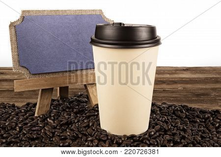 Cup of coffee and coffee beans on an old wooden table, isolated on white background.