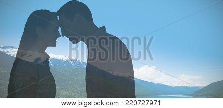 Smiling couple touching foreheads against idyllic view of lake and mountains