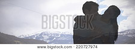 Cute couple smiling at each other against scenic view of snowcapped mountains