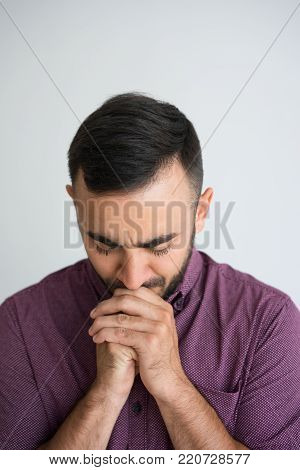 Closeup portrait of thoughtful young handsome man thinking hard with his hands clasped and eyes closed. Contemplation concept. Isolated front view on white background.