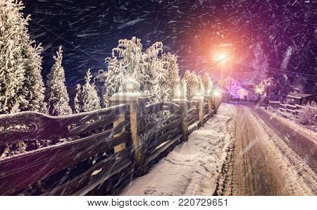 fantastic winter, night scene. Snow Storm over the village. frosty evening. frosty trees over the road, with lights outdoor. unusual wonderful landscape. instagram filter