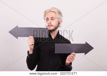 Planning, directions, choices concept. Terryfied, worried man holding black arrow pointing left and right, opposite directions. Indoor shot on light background