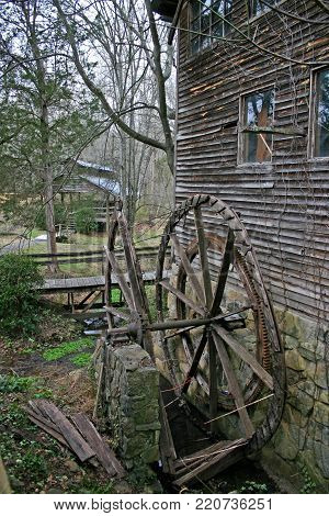 a decrepit waterwheel on an old neglected gristmill
