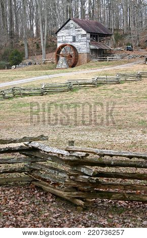 an old gristmill with a rusty wheel behind a split-rail fence