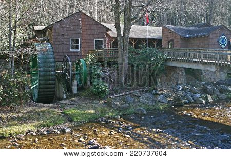 a gristmill with a green metal wheel, beside a stream