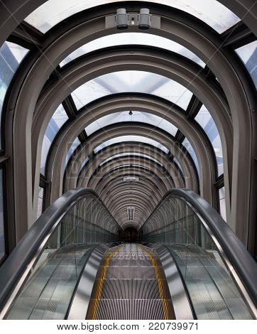 Diminishing perspective in a futuristic escalator tube, where does this tunnel bring us to?