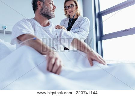 Medical doctor explaining medical scan result to female patient in his clinic. Medicine practitioner showing x-ray to woman and discussing the health condition.