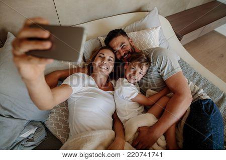 Loving Family Taking Selfie On Bed