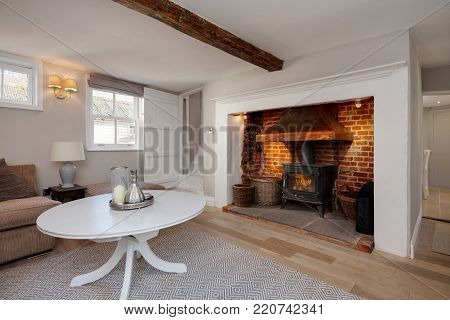 Beautiful Cottage living room with traditional redbrick fireplace containing a cast iron stove and simple surround decorated in shades of white