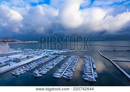 Otaru, Hokkaido, Japan - 29 December 2017 - Boats dock at Otaru Port Marina, Otaru, Hokkaido, Japan on beautiful cloudy blue sky winter day of December 29, 2017