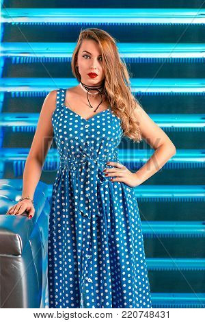 beautiful attractive pretty long haired young woman in polka-dot blue dress and in stockings and red shoes in pin up style on the blue background