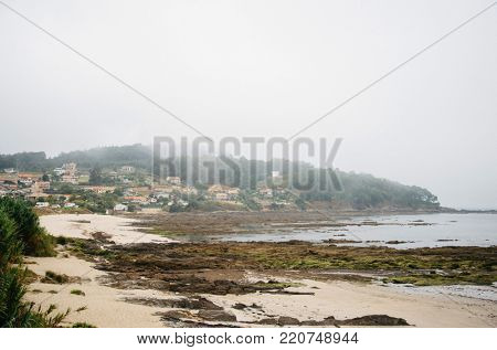 Beautiful beach Praia de Patos in fog weather at low tide. Seascape with houses on the hill background in Nigran, Galicia, Northen Spain.