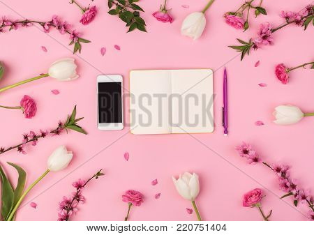 business lady, office, freelance concept. top view of the most important things for businesswoman, there is mobile phone and small clean planner for composing daily life, they are placed among flowers