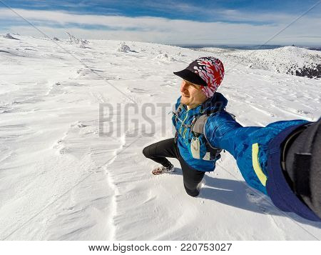 Trail runner selfie in winter mountains, snow and white mountains. Young happy man with backpack cross country running in mountains. Trail runner in powder snow adventure outdoors.