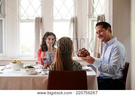 Jewish man holding challah bread at Shabbat meal with family