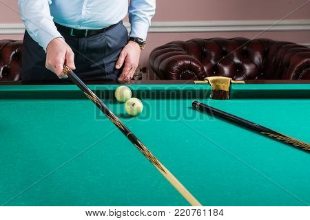 Man with cue opposite to Russian billiard table. billiard player ponders blow