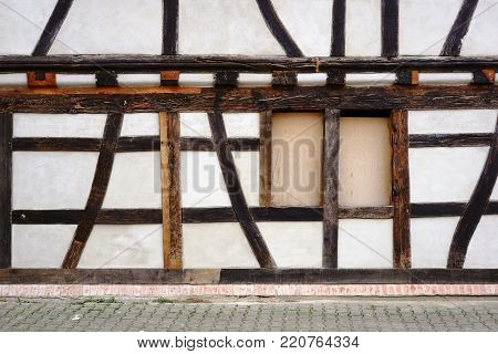 The beam construction and the timber frame of a half-timbered house with a nailed window.