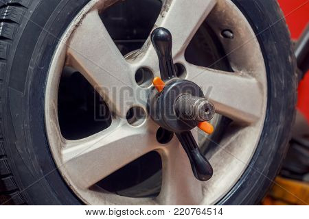 Technician work with mechanic balancing wheel. Installing wheel process close up
