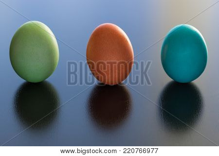 Three dyed Easter eggs are standing up on a black surface. They are green, red, and blue.  They cast a shadow on the table