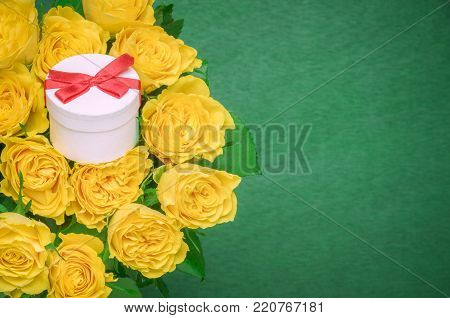 Roses bouquet and a gift box - Beautiful yellow roses bouquet and a cute little white gift tied with red ribbon and bow in the middle, on a dark green wooden background.