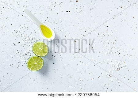 Lime, olive oil and sea salt on gray background; symbolic image