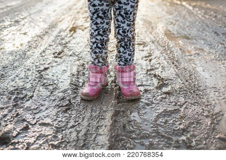 Concept is a happy childhood, child in swamp, children's fun, dirty shoes, life in the village, sunlight, backlight, Ukraine