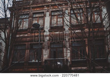Old rusty facade of dark abandoned no man's house with partly broken windows and balcony in center; bare winter trees and solitary lantern in front of house, vibes of despondency, despair, and fear