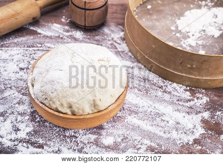 dough made of wheat flour in a wooden bowl on a table, behind a sieve