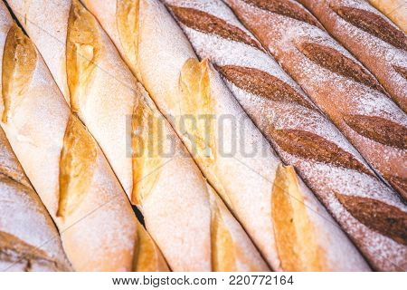 Wheat and rye baguettes lie side by side. Fresh baguettes lie on a wooden table. Baguettes of different flour lie close to each other closely.