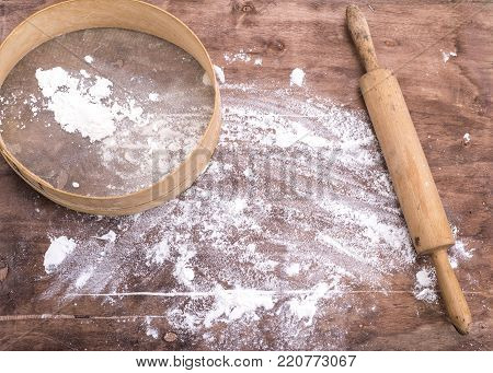 wheat flour sprinkled on a brown wooden table, next to a wooden rolling pin and a round sieve, top view