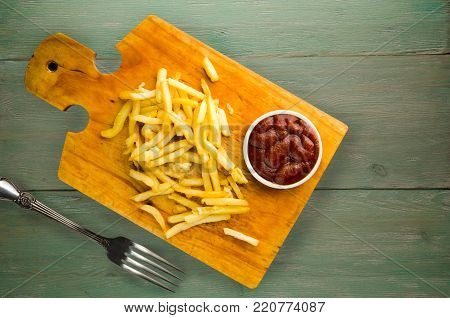 french fries with ketchup on a wooden background. french fries on a plate
