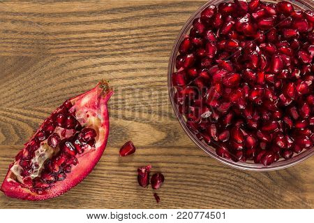 The seeds from a pomegranate fruit in a bowel.  A piece of pomegranate is beside the bowel