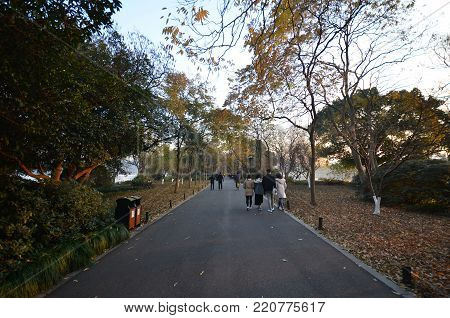 HANGZHOU, CHINA - DEC 26, 2017: People are walking along the embankment of the West lake in Hangzhou China