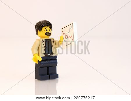 Colorado, USA - January 5, 2018: Studio shot of Lego minifigure businessman staring at a stock chart with scared look on his face.
