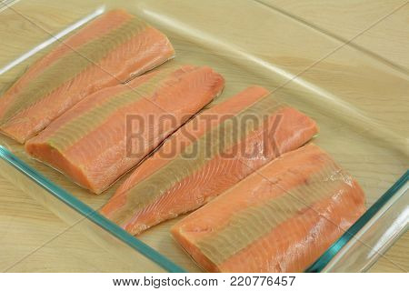 Raw salmon fish fillets on glass baking dish in preparation for making casserole dish