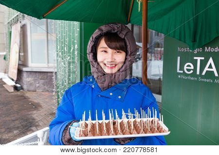 Otaru, Hokkaido, Japan - 30 December 2017, Happy Japanese woman standing in front of Le Tao, chocolate shop, with tray of chocolate samples for customers to try on the cold winter day of  December 30, 2017 in Otaru, Hokkaido, Japan