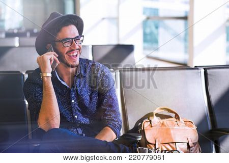 Young traveler sitting in an airport, with a leather briefcase and laughing while talking on his smartphone