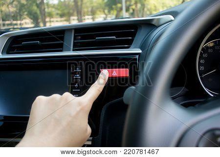 Finger hitting car emergency light botton in car.