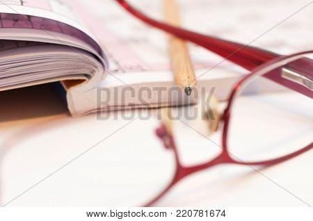 Sharp pencil in focus, eyeglass and crossword close up macro shot.